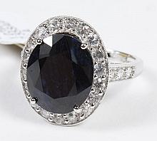 WHITE AND BLUE SAPPHIRE RING - The central oval faceted 7.55 ct midnight blue sapphire is prong set within a bezel of white (colorle...