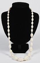 CARVED BONE BEAD NECKLACE - This cream color carved bone necklace of individually carved beads in graduated sizes terminates in a bo...