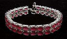 RUBY AND SILVER DOUBLE STRAND BRACELET - A flexible sterling silver ribbon bracelet is formed of two rows of oval pinkish-red rubies...