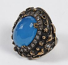 OTTOMAN STYLE BLUE QUARTZ RING - The central oval stone is a faceted blue quartz of exceptional color, encircled by small clear sapp...