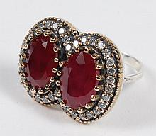 LADY'S DOUBLE-RUBY RING - Two oval, multifaceted pink-red rubies are prong-set side-by-side and surrounded by a tier of clear round ..