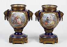 PAIR OF SEVRES STYLE PORCELAIN URNS - Gilt bronze mounted urns with cobalt ground and center medallions painted with floral and roma...