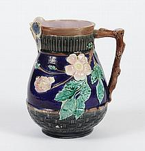 ANTIQUE MAJOLICA WILD ROSE PITCHER - With butterfly lip and raised wild roses on a cobalt ground; pink glazed interior. Apparently u...