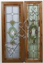 TWO ANTIQUE LEADED AND STAINED GLASS WINDOWS - One window with green, gold and clear glass in a stylized floral design; in a wood fr...