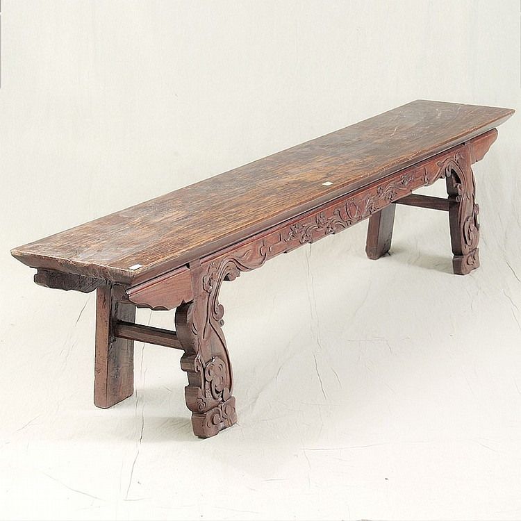 LONG BENCH - Antique Chinese elm with one-piece plank top, relief-carved front skirting, trestle-style legs with stylized cloud and...