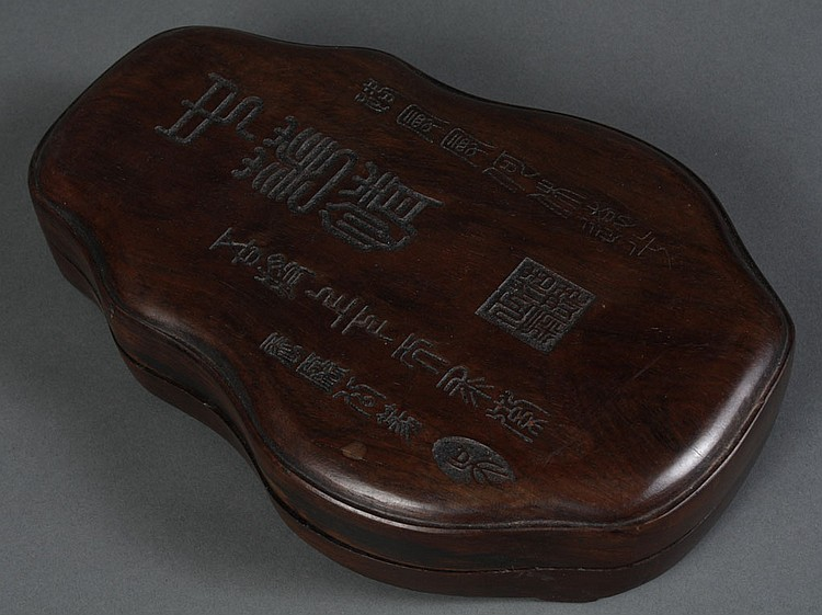 CHINESE INKSTONE IN WOODEN BOX - Inkstone resides in a shaped wood box which has calligraphy on the cover. With seal mark to box cov...