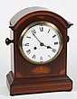 MAHOGANY MANTEL CLOCK - Inlaid mahogany bonnet top clock with enameled face and Roman numerals. The cast works are embossed