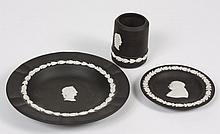 THREE WEDGWOOD BLACK JASPERWARE ITEMS - Comprising a small cup with a neoclassical bust image; a small plate with an oak and acorn t...