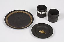 FOUR WEDGWOOD BLACK BASALT ITEMS - Comprising a small tray with gold crocodiles in an Egyptian Revival pattern in the center, a plat...