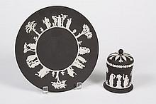TWO WEDGWOOD BLACK BASALT JASPERWARE ITEMS - Comprising a plate and a covered jar both black basalt and decorated with a Greek/Roman...