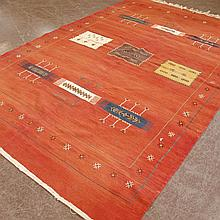 CARPET: HANDWOVEN FLATWEAVE GABBEH - Wool on a cotton warp with a series of geometric designs on a red field inside a border of styli..