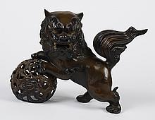 JAPANESE BRONZE FU DOG - Resting a paw on a detached sphere; dark brown patina. Marked