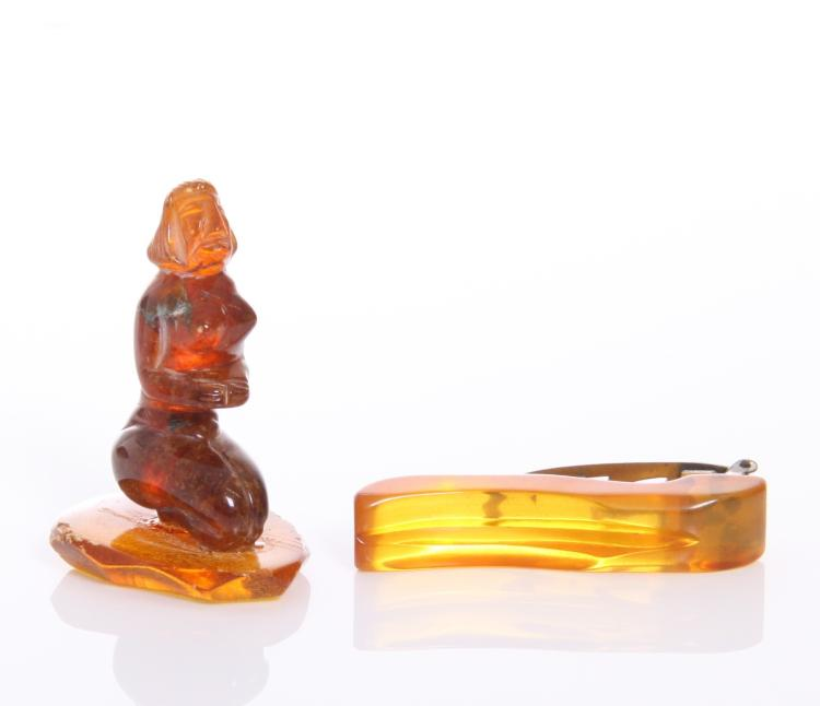 An amber carved figure of a kneeling nude woma
