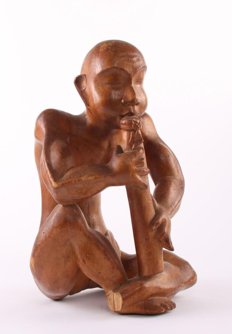 Indonesian wood sculpture carving of a man pla