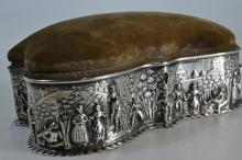 Neat Edwardian Chester hallmarked silver repousse serpentine shaped jewellery box with hinged velvet cover, satin interior and velvet lined. Exterior chased with continuous band of figures within village scene. Dates to 1904 AR