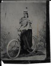 1870s tintype of a woman and bicycle