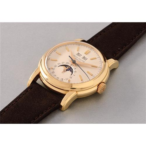 PATEK PHILIPPE - A very fine and extremely rare yellow gold perpetual calendar wristwatch with phases of the moon, screw-back, center seconds and