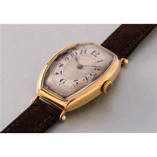 PATEK PHILIPPE - An extremely rare and elegant tonneau-shaped yellow gold wristwatch with hinged case, 1908 / 1920