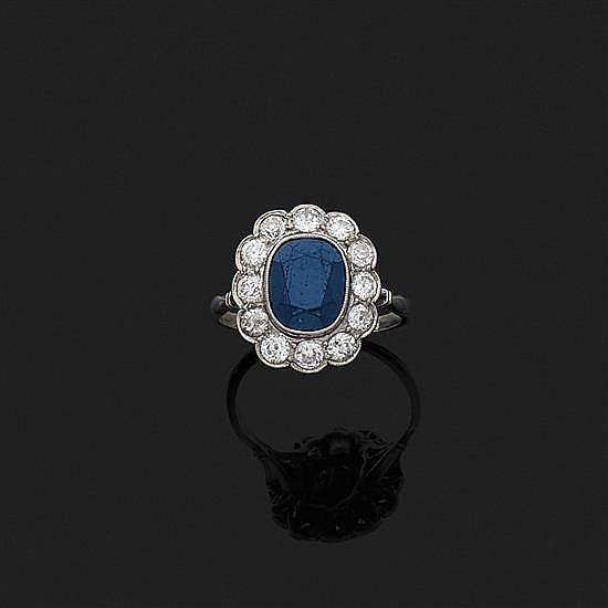 Bague en platine 850‰ ornée au centre d''un saphir ovale dans un entourage de douze diamants ronds.(Egrisures au saphir).
