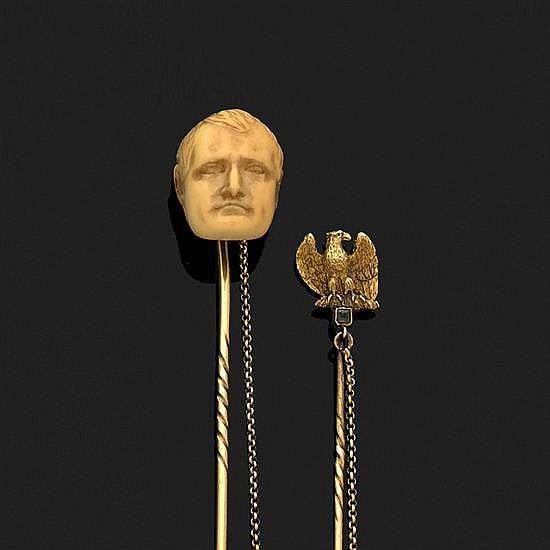 Deux épingles de cravate en or l''une à tête de Napoléon en os sculpté, l''autre à décor d''aigle impérial. On joint une clé de montre