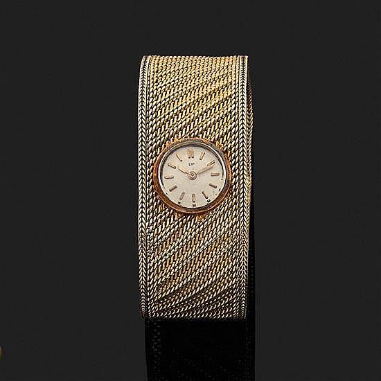 LIP.Montre-bracelet de dame en or jaune 18k, 750‰ le cadran rond inclus dans le bracelet. Tour de bras souple en tissu d''or tressé.