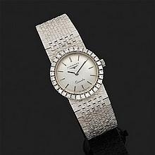 LONGINES.Montre bracelet de dame en or gris 18k, 750‰ cadran rond, lunette sertie de diamants. Tour de bras souple en or gris satiné.