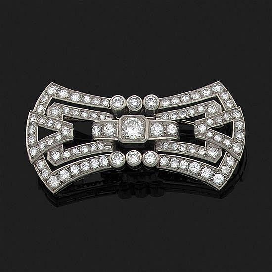 Broche plaque en platine 850‰ à décor géométrique ajouré ornée de diamants taille brillant dont un plus important au centre.Vers 1930.