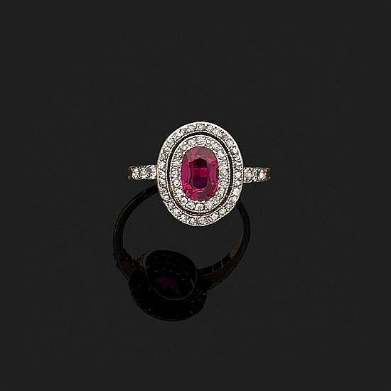 Bague en or jaune 18k, 750‰ et platine 850‰ ornée d''un rubis ovale dans un double entourage de diamants taillés en rose