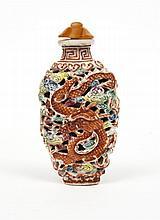 Flacon tabatière de forme balustre, en porcelaine émaillée polychrome et or, moulée et réticulée d'un dragon et d'un phénix dans les...