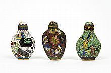 Trois flacons tabatières en émaux cloisonnés polychromes, l'un de forme balustre aplatie à décor d'oiseaux et de fleurs sur fond ver...