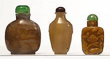 Ensemble de trois flacons tabatières en agate, l'un de forme carrée arrondie en agate mousse à veines blanches; l'un piriforme, inci...