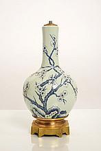 Vase de forme bouteille en porcelaine émaillée céladon et décorée en bleu sous couverte de branches de pruniers en fleurs