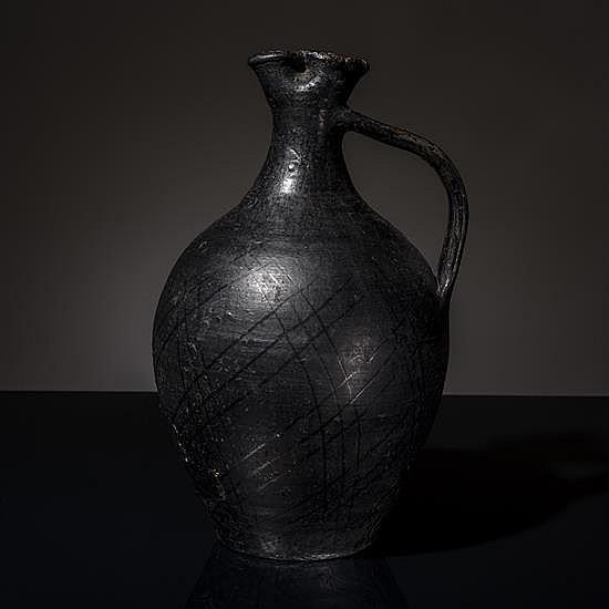 Vase en majolique noire, de forme ovoïde, le bectrilobé et l'anse plate ; décor de croisillons.