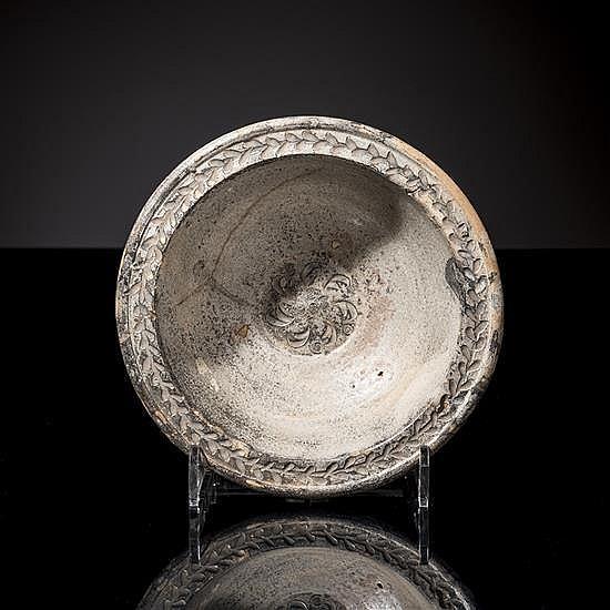 Coupe en céramique gris-bleutée, le centre ornéde pétales, bordure à décor d'une guirlande de