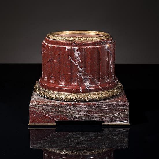 Petite base en marbre rouge griotte veinégris, de forme circulaire, le fût cannelé, la