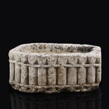 Petit sarcophage en pierre calcaire sculptéetoutes faces à décor géométrique de demi-colonnes et de pointes.