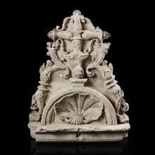 Fronton de lucarne en pierre calcaire sculptéeen fort relief. Tympan semi-circulaire orné