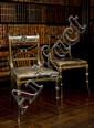 Paire de chaises en bois peint en noir et doré à dossier ajouré et décor de mufle de lion ; les pieds façon bambou ; marquées IB en cre