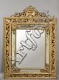 Miroir à parecloses en bois sculpté et doré ajouré de rinceaux, feuillages et palmettes, le fronton décoré de feuillages et fruits. Tra