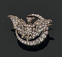Broche en or et argent, figurant une chauve-souris aux ailes déployées, inscrite dans un croissant de lune, entièrement sertie de di...