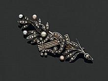 Broche en or et argent, décorée au centre d'une lyre entre deux motifs feuillagés, l'ensemble serti de diamants taillés en rose et d.