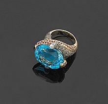 Bague en or 18 k et argent sertie d'une topaze bleue traitée de forme ovale, les griffes pavées de diamants taillés en rose et de sa..