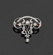 Broche en or jaune 18 k et platine ajouré, à décor d'entrelacs et d'agrafes, entièrement sertie de diamants taillés en rose et de ta.