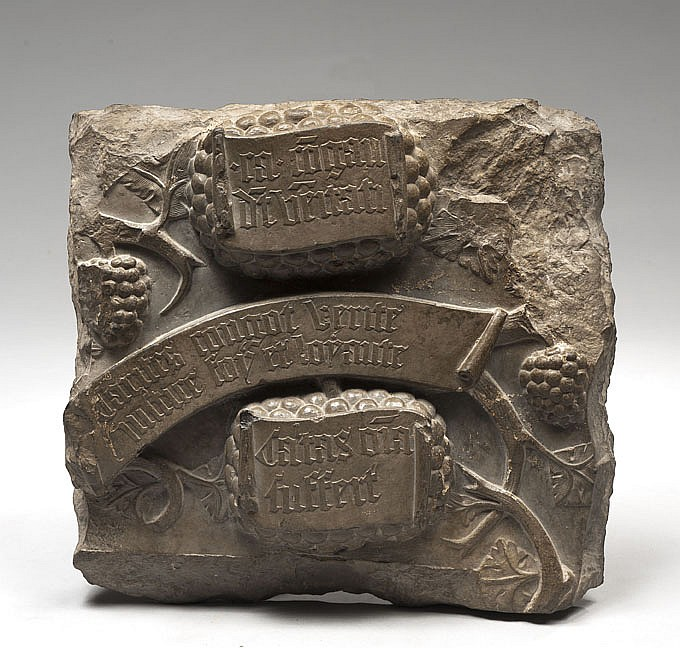 Fragment de pierre tombale (?) en pierre calcaire grise à grain fin sculptée en fort relief de pampres et de phylactères avec inscripti