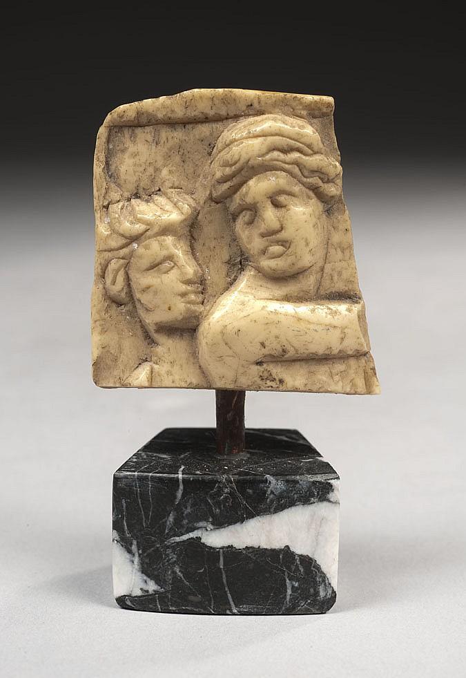 Fragment en os sculpté représentant deux têtes de personnages, l'un au buste nu tournant son visage vers un autre qui le regarde