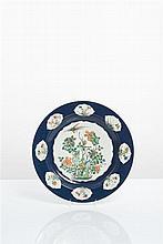 CHINE - Epoque KANGXI (1662-1722) Grand plat en porcelaine décorée en émaux polychromes de la famille verte d'un oiseau volant au-dess