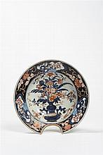 JAPON, Imari - XVIIIe siècle Plat à barbe en porcelaine décorée en bleu sous couverte, rouge de fer et émail or d'un vase fleuri au ..