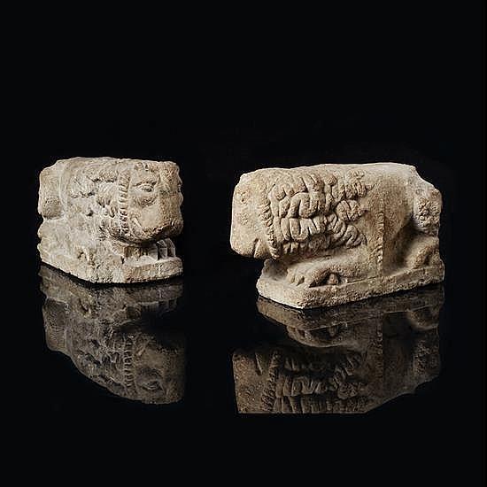 Paire de lions en pierre calcaire sculptée. Ilssont couchés, leur tête légèrement tournée sur