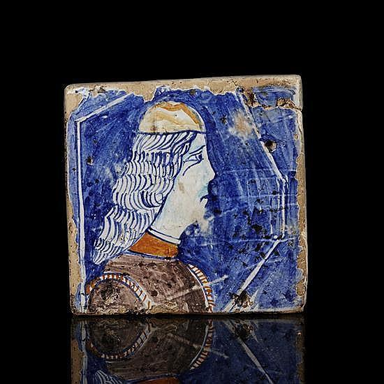Carreau en faïence polychrome à décor d'unprofi d'homme tourné vers la droite, fond bleu.