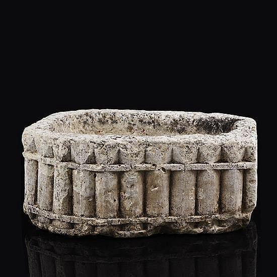 Petit sarcophage en pierre calcaire sculptéetoutes faces à décor géométrique de demicolonnes et de pointes.